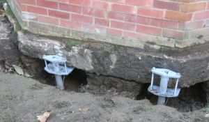По периметру дома вкручивают винтовые сваи на глубину до двух метров.