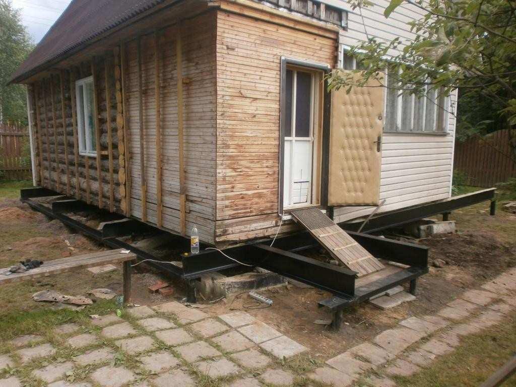 Дом на новом свайно-винтовом фундаменте. Для поднятия дома над фундаментом используется строительное оборудование