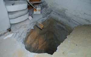 Разведочный шурф в подвале здания для обследования состояния фундамента