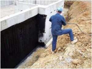 Процесс обработки фундамента дома гидроизоляционной резиной
