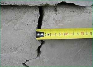 Измерение размеров трещины в ленточном основании дома